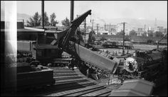 Caption: View from up on roof of the roundhouse showing the rerailing tender of NP 5126 after sticking throttle caused tender to drop into the Missoula Turntable Pit. NP Wrecker 44 on duty. Looks like a Class Q engine sitting on Turntable.  Date: June 22, 1942       Location: Missoula, MT       Photographer: Ron V. Nixon  Railroad: Northern Pacific Railway       Station: Missoula --- USA