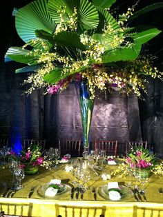 Shaped palm fronds with orchids in a unique vase for the reception. Gorgeous!
