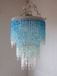 model- The Trinidad Bay  17 in diameter 32 in height 3 lights  Glorious aquamarine blue cascades from the top of this exquisite fixture, foaming into lighter shades as the eye descends, evoking the impression of flowing, living water. Each piece of cultured sea glass is accented by tiny clear glass beads like water drops, and the New Orleans-style frame features cast-metal scrolling arms.  The Trinidad Bay can be mounted semi-flush to the ceiling or chain hung as a chandelier; please…