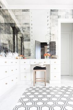 Black double doors open to a black and white bathroom featuring a single wall vanity, divided into ...