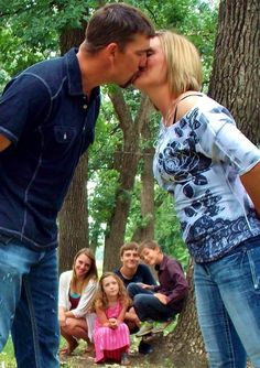 Parents kiss with kids in the background. Family photo idea. Kiss. Couple photos.
