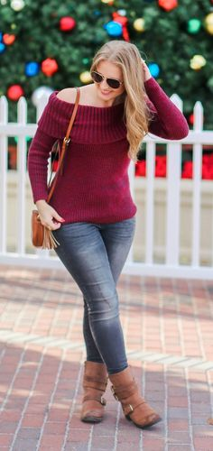 Rose gold aviator sunglasses from Foster Grant, off-the-shoulder burgundy sweater, distressed grey jeggings, distressed moto booties, and cognac tassel crossbody handbag styled in a casual winter outfit by Florida fashion blogger Ashley Brooke Nicholas. S