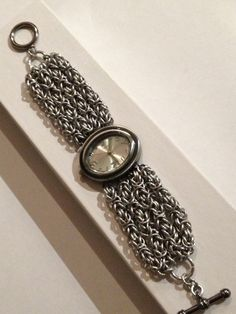 Silver toned watch with Byzantine multi strand band - anodized aluminum rings