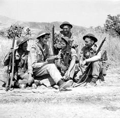 Capt SB East, a chaplain, talks with soldiers of the 48th Highlanders, 1st Canadian Infantry Division, near Regalbuto, Sicily, in July 1943.