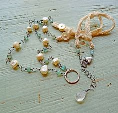 nina bagley - baroque pearls and fluorite beads with sterling wire, a couple of lengths of antique tea-dyed lace with antique mother of pearl buttons, at the chain's end is a faceted moonstone briolette drop