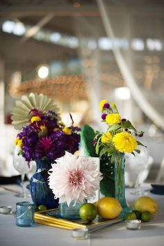 i was so happy with the table arrangements. we collected mismatched blue glass vases leading up to the wedding, and stacked them on old national geographic magazines. our florist & wedding planner had the idea of surrounding them with loose lemons and limes, which i thought was really fun.
