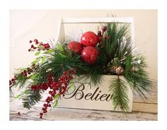 BELIEVE    This holiday arrangement will be a great addition to your Christmas decor    I have painted this wooden caddy a beautiful creamy country white and then added vinyl lettering to the front. Filled with pine greenery, red berries, pinecones, flocked pine sprigs and 3 red ornaments.    Box is 12.5 tall and arrangement span is approx. 21    Perfect for any country or cottage Chirstms decor.....set near a fireplace, enclosed porch or just about anywhere.    Shipping price listed is for…