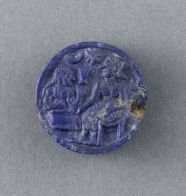 Token with a love scene. circa 2400-2200 BC. Southeast Iran. Probably an ornament, even if its real destination is still unknown, this precious little token made of lapis lazuli takes the form of a thick disc, pierced through the side, and has a carved relief on both faces. The edge is decorated with two torsades with three strands at each end of the hole, where the remains of a heavily corroded copper thread or wire are visible.