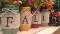 Paint Mason jars then wrap them in burlap to act as rustic vases for fall foliage and florals. Learn more at Midnight Owl Candle Co.