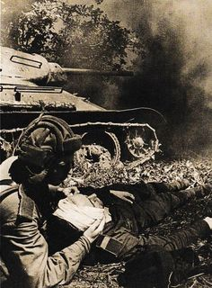 World War II. A Soviet soldier from a stricken T-34 tank provides the first aid for his wounded comrade. The Battle of Prokhorovka, 12 July 1943, Russia.