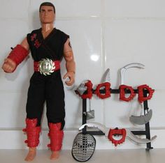 "ACTION MAN: Power Arm Ninja (1995) INCLUDES: 12"" action figure with spinning wrist action, Ninja grill mask, black ninja uniform, red shin guards, five authentic looking Ninja weapons, weapons rack, and Power Arm belt NOTE: Belt can be worn as a child's wrist band. Comment: ""The Saw-Sword may be one of the coolest weapons ever!"""