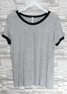 Totally loving this super (extremely) soft heather gray basic tee. Quality tee features black rimmed hems and heather gray body. Tee has a loose fit and looks so good with boyfriend jeans! Or tie it on the side and wear with highwaisted denim shorts, a flannel, and thigh high socks. The best basi...