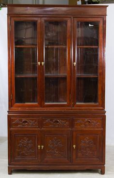 Lot 127: Asian Carved Rosewood Stained China Cabinet; Two piece cabinet with upper section having three wood framed glass doors with interior shelving, lower section having three 1/3 carved drawers over three carved wood panel doors