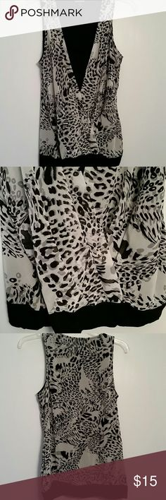 Black and white leopard printed tank Previously worn but in great condition.  This blouse consists of a solid black shell with the leopard printed cover sewn over the top of it.  There is a black band around the bottom. The black piece is t-shirt material and the leopard printed piece is a thin chiffon like material.  Both materials are very soft. Garment must be hand washed. Express Tops Tank Tops