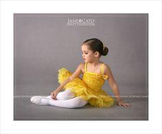 Little ballerina dancer in yellow tutu with bun.