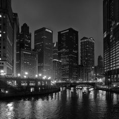 Black and white photograph of the downtown Chicago skyline at night, with city lights reflecting in the black Chicago River. (Square format) Standard Prints: - Printed on real silver-based Resin Coate