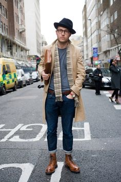 New-school cool. | Tags: fall/winter, layers, tan, mid-length, wool pea coat, basic gray t-shirt, cuffed blue jeans, denim, brown leather boots - Accessories: black fedora, hat, glasses, purple & green plaid scarf, fringe, brown leather belt, wristwatch, brown leather watch strap, brown leather laptop bag, clutch - Misc.: outside, street, concrete, city
