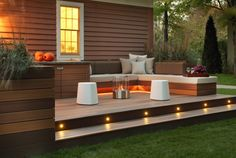 Inspiring Deck Lighting for Outdoor Lighting Ideas : Brown Siding Plus White Trim Window Also Outdoor Living Space With Deck Outdoor Fireplace And Gray Pillows On Bench Plus Seat Cushion Also Ottoman Tray With Pumpkins Decor And Stair Lighting