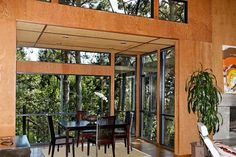 The formal dining room is surrounded by windows and looks out at mature trees. Photo: Obeo