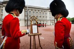 Troops look at the birth announcement at Buckingham Palace