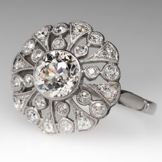 """1920'S ART DECO COCKTAIL HALO RING SNOWFLAKE MOTIF The ring is centered with a 1 carat old European round cut diamond and it is stunning. The diamond has a gorgeous sparkle and grades I in color and SI2 in clarity. The openwork mounting is encrusted with diamonds and finished with mil grain detailing. This solid platinum ring features an elegant low profile design and is beautifully made. Signed with makers mark """"B&S""""."""