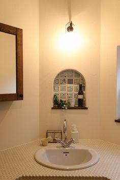 壁面にモザイクタイルをあしらったアーチ型のニッチがかわいいサニタリースペース。