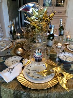 Closeup of New Year's Eve tablescape. Includes new: small watch plates (222 Fifth, Time Will Tell), medium watch plates (made in China, gift shop), gold chargers and Paris napkins (Home Goods), & cupcake stands (Pottery Barn). Chrystal is vintage. Under the watch plates are Lenox white China (Tin Pan Alley) with black etchings of either the Eiffel Tower, Statue of Liberty & Big Ben (Macy's- also have Golden Gate Bridge).