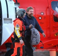 Louis Jordan, 37, walks under from the Coast Guard helicopter to the Sentara Norfolk General Hospital in Norfolk, Virginia after being found on the overturned hull of a sailboat 200 miles off of the North Carolina coast. Jordan had been missing since January. <span class='credit'>(Steve Earley | The Virginian-Pilot)</span>