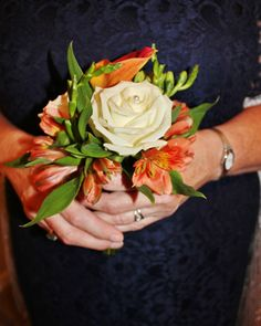 In place of a corsage, the mothers carried small clutch bouquets of alstroemeria, white rose, and tangerine mini calla. By Rockwall Wedding Chapel, Rockwall, TX www.rockwallchapel.com