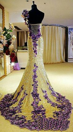 WOWSER, WOW, WOW. This gown is so over the top gorgeous....., I don't know where to start. The colors are dynamite, being a lemon yellow and a medium purple. The embellishments cannot be beat. The bare back on this gown, gives it even more glamour. I cannot wait to see what the front looks like? Eccentric, but Exceptional !!!