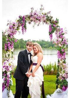 Pretty purple and lavender flowers in this wedding arch