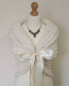 A beautiful and versatile ivory bridal shawl or wedding wrap that can be worn in many different ways. This lovely bridal cover up is the perfect shawl for your wedding dress. This crochet shawl closes with a double-faced premium satin ribbon, which ties into a delicate bow. This wrap is perfect for many occasions from formal to casual: weddings, parties or just as an everyday wrap.  I make this cape in many colours but if you cant find what you need, just let me know. If you want me to…
