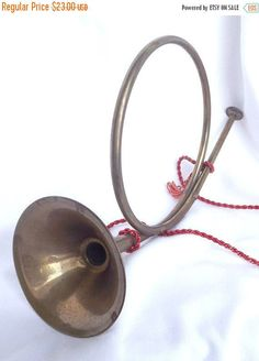 Festive brass french horn on red rope with tassels. A wonderful ornament for the holiday season. Measures 12 inches x 7 inches. Good vintage condition, consistent with age. Aged with Grace