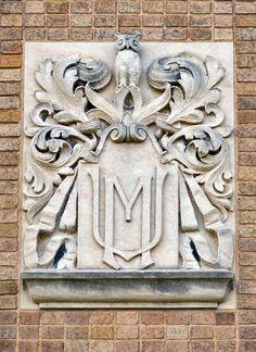 Stone-carved Marquette University emblem on Sensenbrenner Hall.
