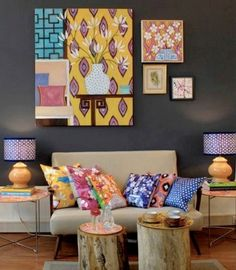 Preto na parede serve como base para quadros coloridos, sofá claro e almofadas estampadas da sala