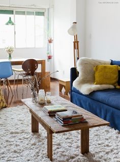 Um casal conseguiu transformar um apartamento alugado em um lugar cheio de personalidade através da decoração. A mesa rústica e o sofá azul definem o estilo da sala!