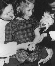 United Nations personnel vaccinate an 11-year-old concentration camp survivor who was a victim of medical experiments at the Auschwitz camp. Bergen-Belsen displaced persons camp, Germany, May 1946.