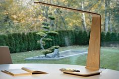 Tunto PowerKiss Lamp;  made from bent, ultrathin wood board, this unique lamp features PowerKiss wireless charging technology built into the base, touch-sensitive sensors for power and light intensity, and nine ultrathin LED lamps to provide plenty of light.
