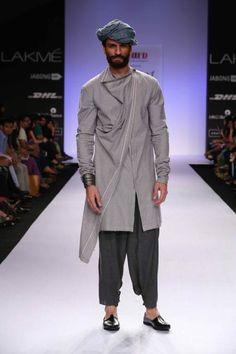 """Lakme Fashion Week 2015 Ujjawal Dubey Next Generation designer and NIFT graduate Ujjawal Dubey's collection called """"No more the Hunted"""" takes inspiration from Middle Eastern Male's attire. Designer offered masculine and rugged for which the material varied from woven to knit. Colour palate was minimal with the selection of shades of green and blue. The collection reflected the men's daily wear that has deep resemblance to Afghani, Turkish and Arab Man. #mennesslife #men #mensfashion2015"""
