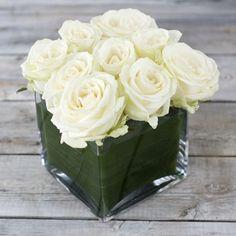 Valkoisia ruusuja lasimaljakossa.