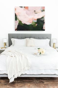 beautiful white bedroom with abstract art above the bed