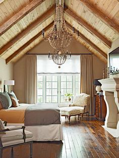 Inviting Aerie - In this master bedroom, the distinctive silhouette of two chandeliers crafted from rustic wooden beads are highlighted by walls upholstered in a woven fabric and windows dressed in the same neutral plaid. A limestone fireplace and beamed ceiling add a sense of warmth and history.