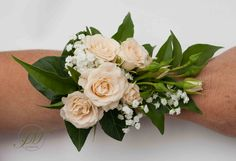 Wrist corsages made of spray peach roses and foliage.