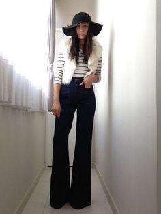 Jeans acampanados con blusa blanca a rayas y sombrero negro boho