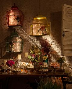 Dessert wedding table, decorated with cages and strings lights, flowers arrangaments, and wall coated with lace