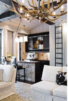antler chandelier, light fixture in kitchen, ladder, exposed beams, contrast in colour, cow hide