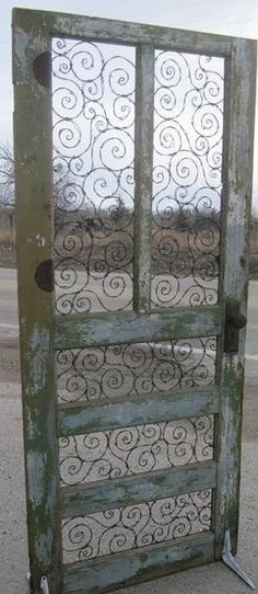 Spirals of Barbed Wire In Upcycled Door. This would make an awesome trellis! Neat idea !
