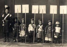 HISTORIC PHOTO - A masquerade was a dance or party where participants attend wearing a costume and often a mask.  These little costumed cuties are all dressed up for a masquerade ball at the Liederkranz in 1908. The signs they hold spell out Rexall, likely the business that sponsored their costumes for the masquerade. From left to right, they are identified as Francis Frietag (age 12), Jennie Heusinger, Pauline Vieregg, Louise Scheel, Heusinger, Elmer Scheel, and John Vieregg.