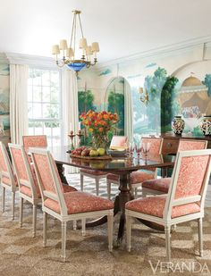 Raquet makes bolder color plays elsewhere. The formal dining room resists predictable tropical decor with an antique Swedish blue glass chandelier but acknowledges the island locale with chairs in a lively coral print and hand-painted canvas murals splashed with sea views and palm trees. Chairs, Andrew Raquet Collection, in Quadrille fabric. Table, Barry Cotton Antiques. Mural, Stark. Chandelier, Evergreen Antiques. Sconce, Hinson Lighting. Max Kim-Bee  - Veranda.com