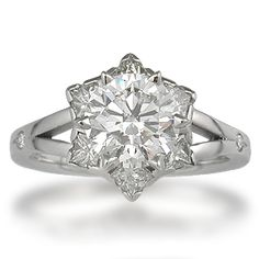 "Artistic Snowflake Engagement Ring - Just like each snowflake that falls from the sky, your Snowflake Engagement Ring will be unique.  The ""snowflake"" consists of six prong-set princess cut diamonds surrounding a round brilliant cut diamond.  The band branches out to support the setting.  Ideal cut accent diamonds."